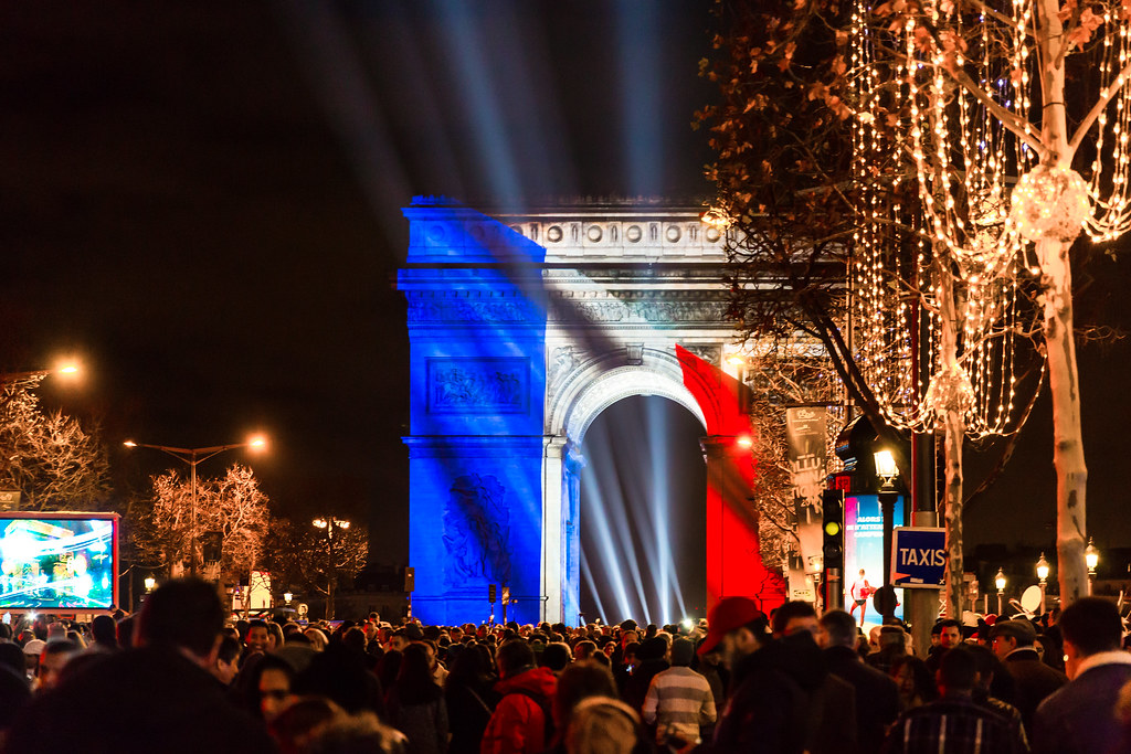 A photograph of the Champs-Elysées on New Year's Eve. The Arc de Triomphe is illuminated by blue, white, and red light. Crowds line the street.
