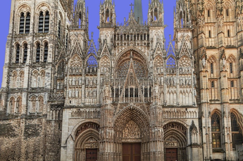 A phtograph of the front façade of Rouen Cathedral during the day